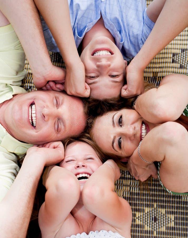 Glückliche Familie, die in einem Kreis liegt stockfoto