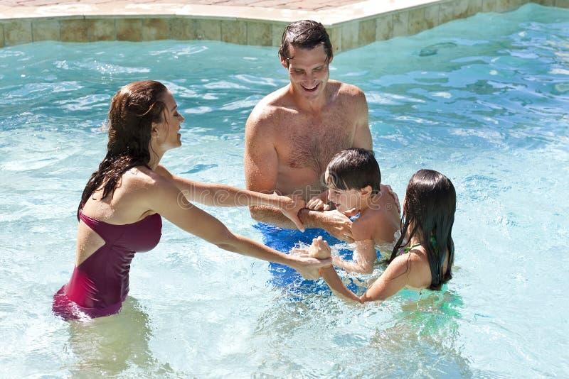Glückliche Familie, die in einem Swimmingpool spielt stockfotos