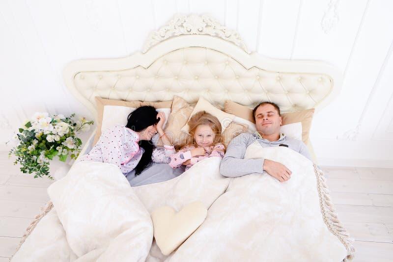 Glückliche Familie, die in einem weißen Bett und in einem Schlaf liegt Mutter, Vater und stockbilder