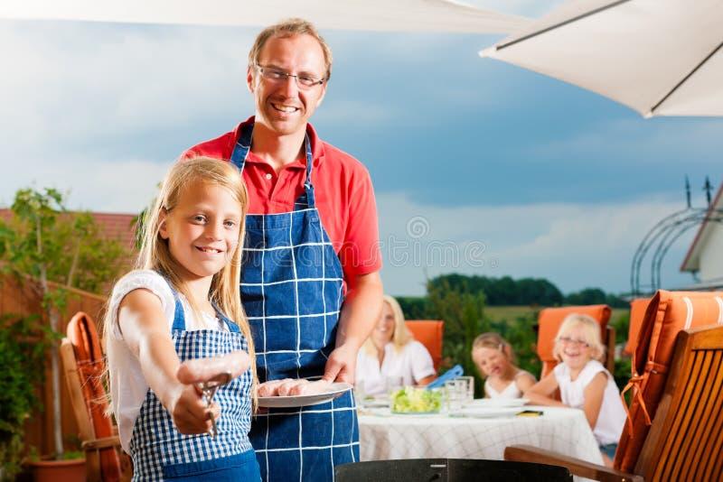 Glückliche Familie, die einen Grill hat stockbild