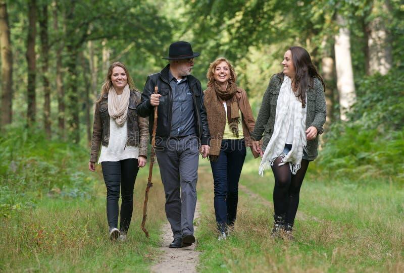 Glückliche Familie, die einen Spaziergang durch das Holz genießt stockfotos
