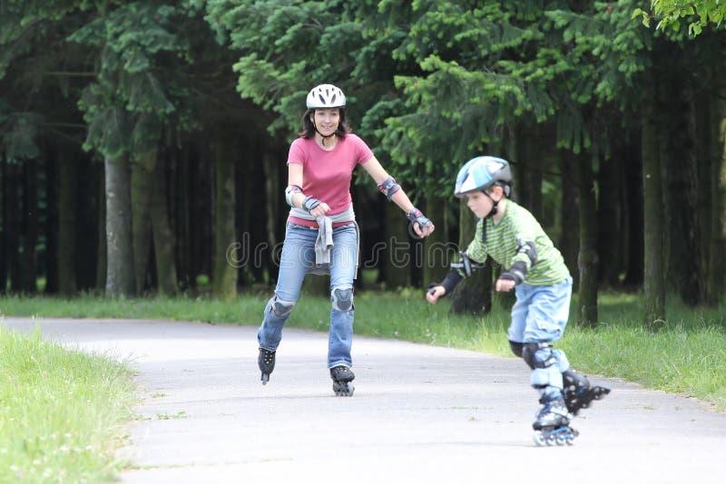 Glückliche Familie, die erlernt, auf Rollerblades zu fahren lizenzfreie stockfotografie