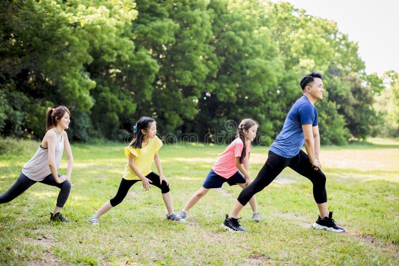Glückliche Familie, die gemeinsam im Park trainiert lizenzfreie stockfotos