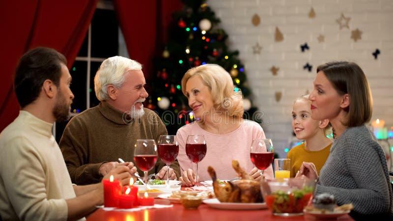 Glückliche Familie, die geschmackvolles Weihnachtsessen zusammen, Lichter auf dem funkelnden Baum hat stockbild