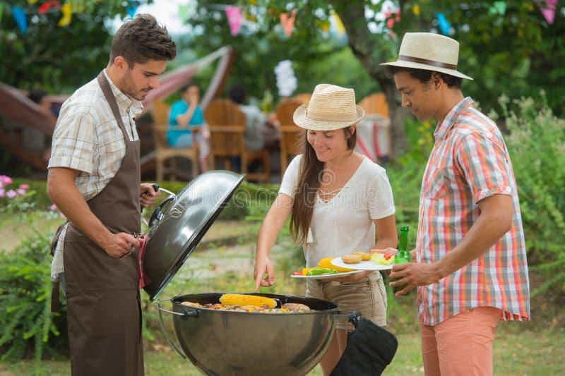 Glückliche Familie, die Grill am sonnigen Tag hat lizenzfreies stockbild