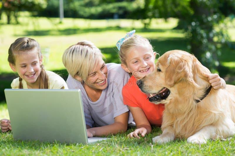 Glückliche Familie, die ihren Hund betrachtet stockfotografie