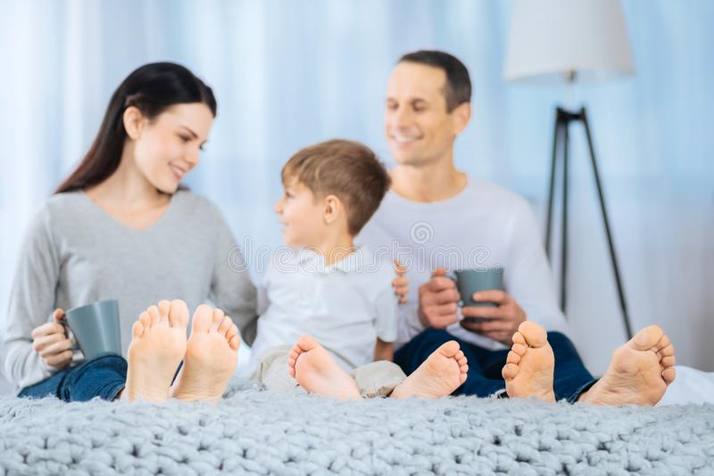 Glückliche Familie, die im Bett beim Haben von bloßen Füßen spricht lizenzfreie stockfotos