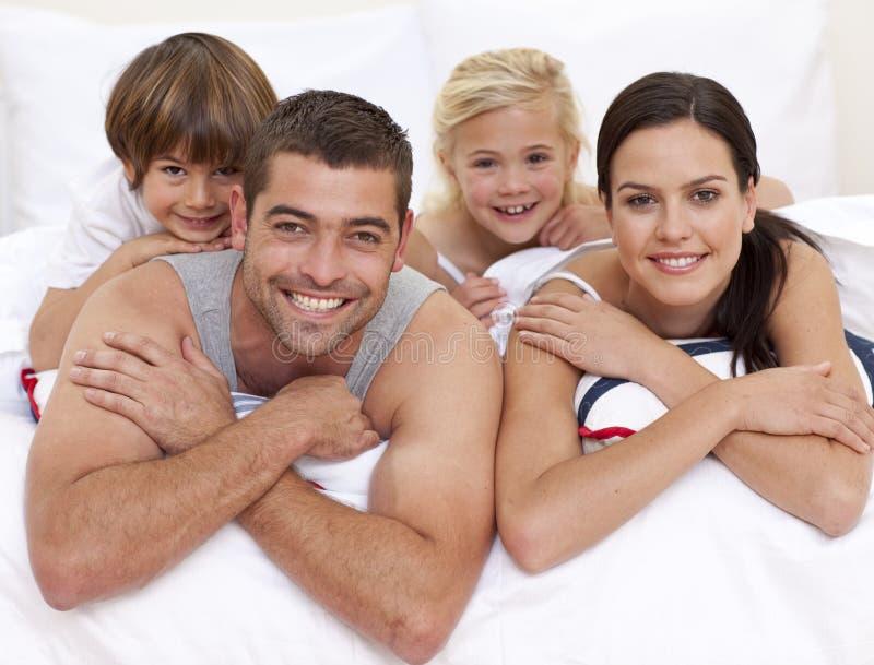 Glückliche Familie, die im Bett der Muttergesellschafts spielt lizenzfreie stockbilder