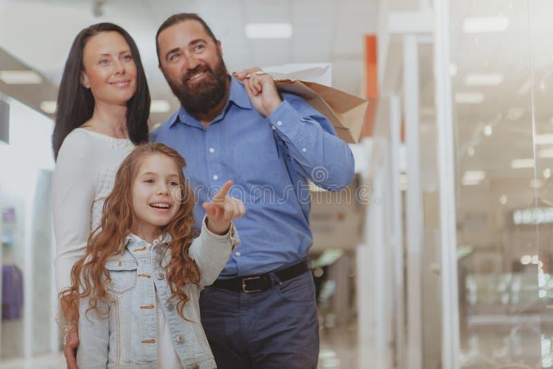 Glückliche Familie, die im Einkaufszentrum zusammen kauft lizenzfreie stockfotos