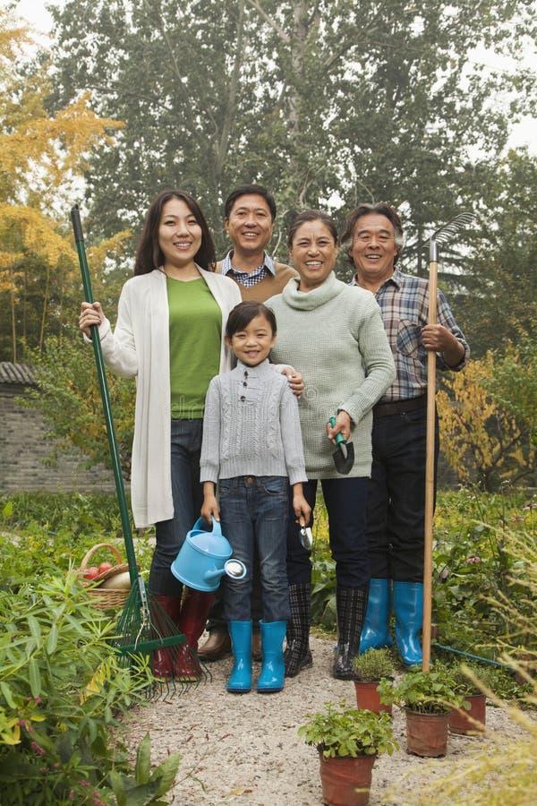 Glückliche Familie, die im Garten arbeitet lizenzfreie stockfotos
