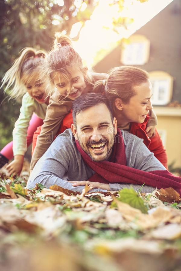Glückliche Familie, die im Herbstlaub liegt lizenzfreie stockfotografie