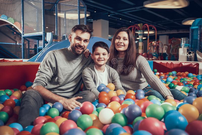 Glückliche Familie, die im Pool mit Bällen sitzt lizenzfreies stockbild