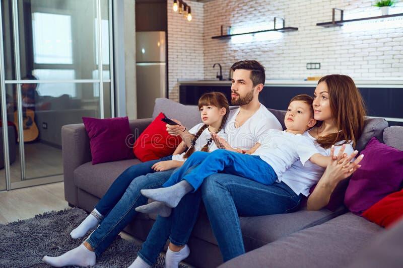 Glückliche Familie, die im Raum sitzt auf dem Sofa stillsteht lizenzfreies stockfoto