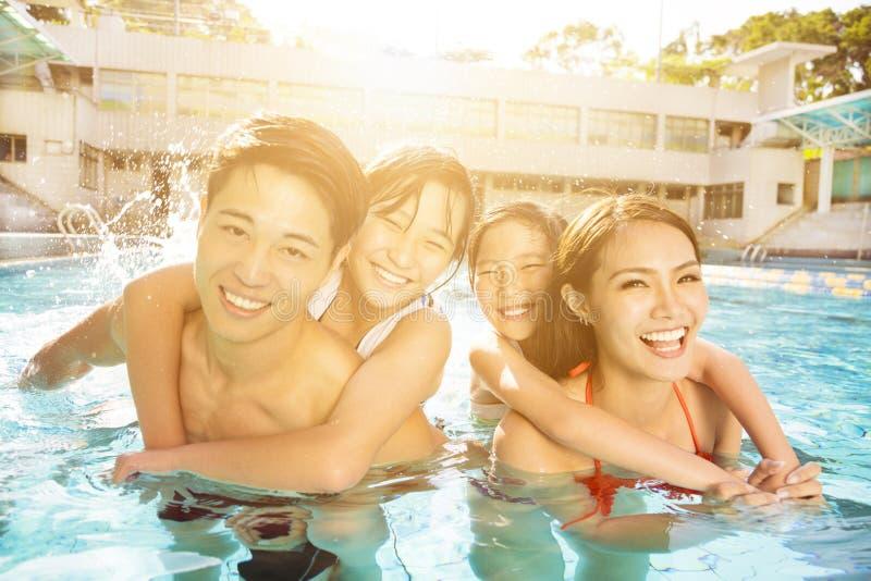 Glückliche Familie, die im Swimmingpool spielt lizenzfreies stockbild