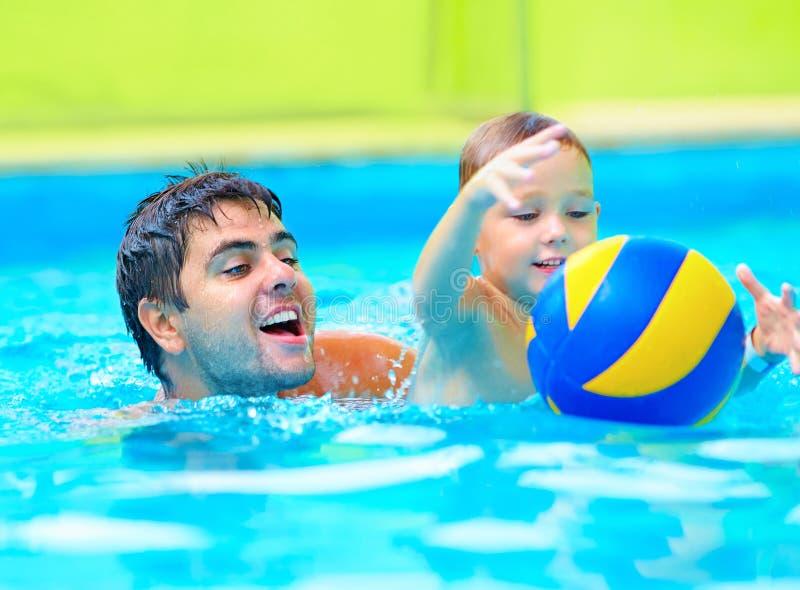 Glückliche Familie, die im Wasserball im Pool spielt lizenzfreie stockfotos