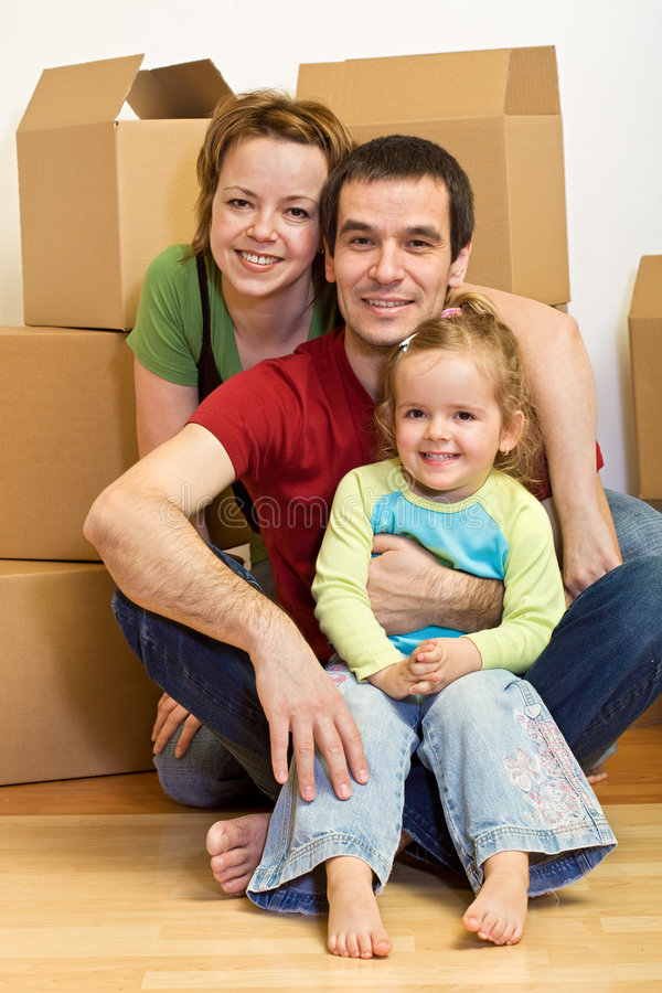 Glückliche Familie, die innen auf dem Fußboden in einem neuen Haus sitzt stockfotografie