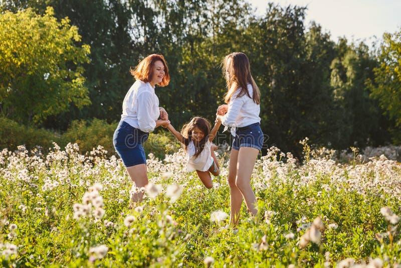 Glückliche Familie, die mit Baby auf dem Rasen im Sommer spielt stockfoto