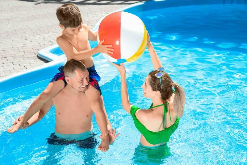 Glückliche Familie, die mit Ball im Swimmingpool spielt lizenzfreie stockbilder