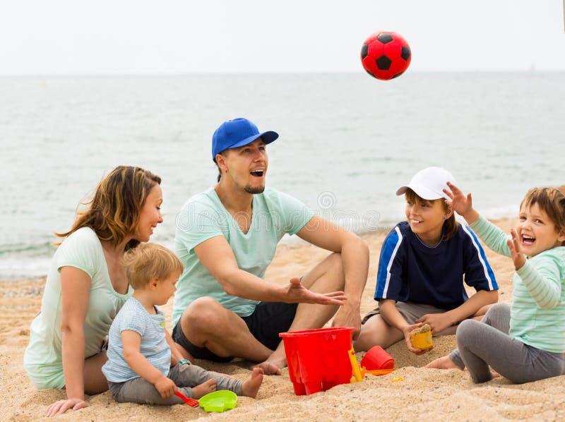 Glückliche Familie, die mit Ball am sandigen Strand spielt lizenzfreie stockbilder