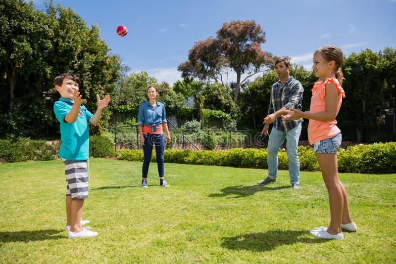 Glückliche Familie, die mit dem Ball im Park spielt stockfoto