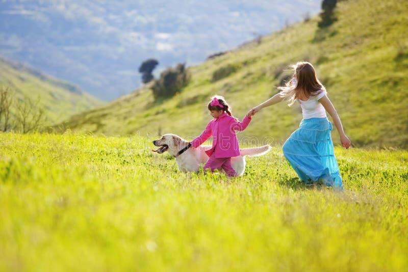 Glückliche Familie, die mit Hund geht stockfoto