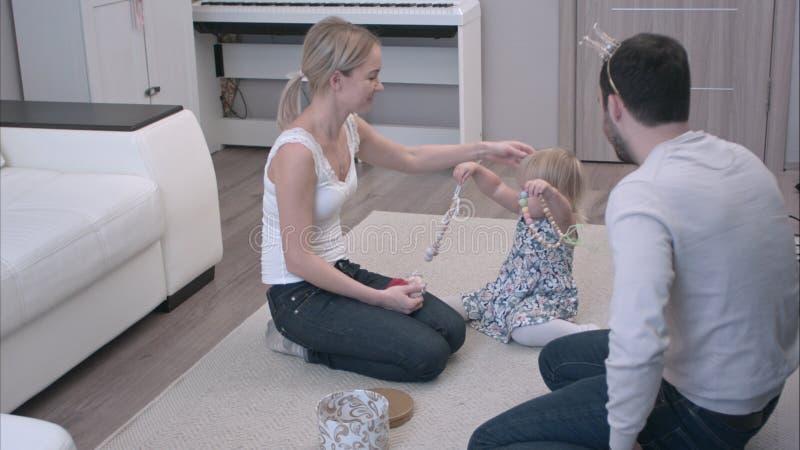 Glückliche Familie, die mit Schmuck mit dem Vati versucht auf einer Prinzessinkrone und seinem kleinen Kind anbieten ihm Halskett lizenzfreie stockfotos