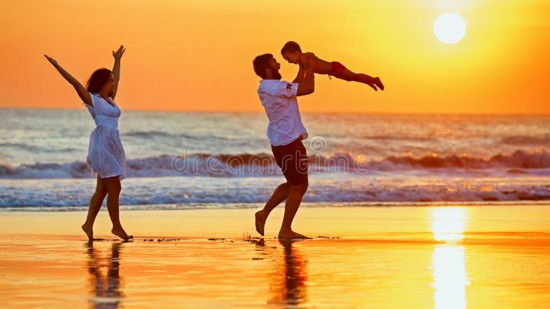 Glückliche Familie, die mit Spaß auf Sonnenuntergangseestrand geht stockfoto