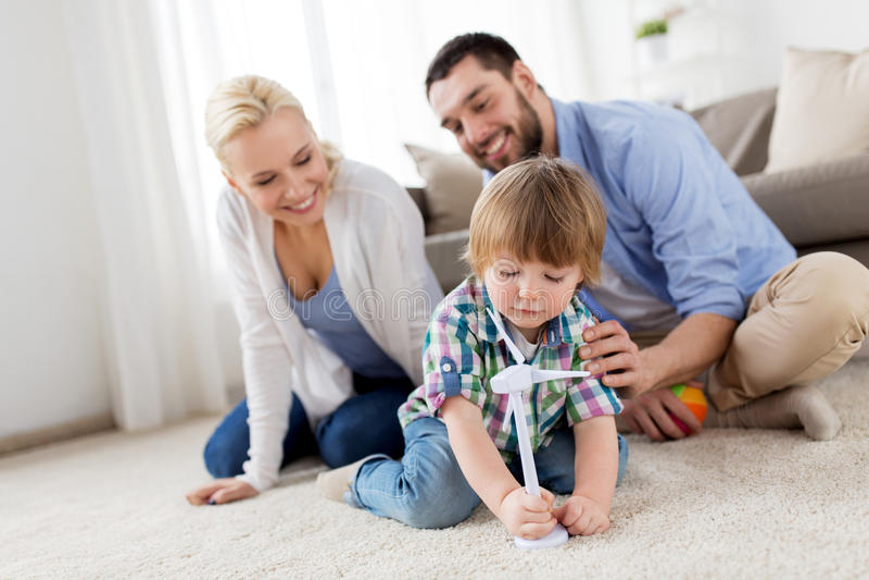 Glückliche Familie, die mit Spielzeugwindkraftanlage spielt stockbild