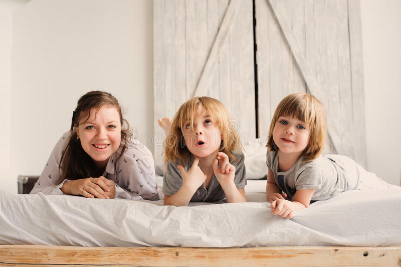Glückliche Familie, die morgens im Schlafzimmer spielt lizenzfreie stockfotos
