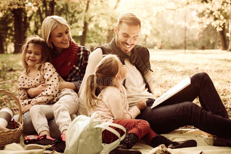 Glückliche Familie, die Picknick hat Unterrichtende Tochter des Vaters zu lesen lizenzfreie stockfotografie