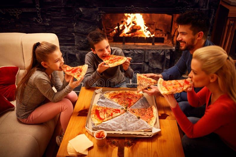 Glückliche Familie, die Pizzascheiben für das Abendessen isst lizenzfreies stockfoto