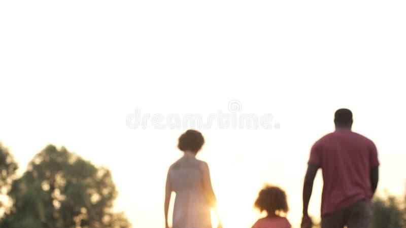 Glückliche Familie, die in Sonnenuntergang, in viel versprechende Zukunft für liebende Eltern und in Kind geht stockbild