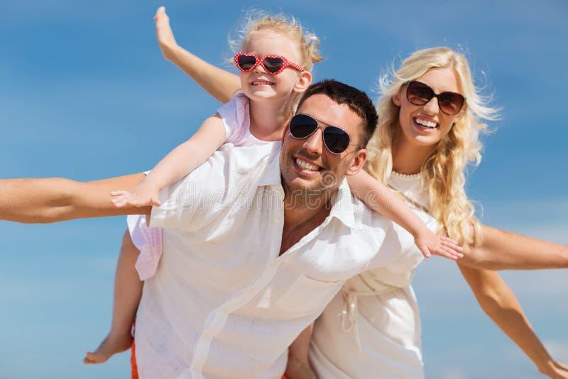 Glückliche Familie, die Spaß über Hintergrund des blauen Himmels hat stockbilder