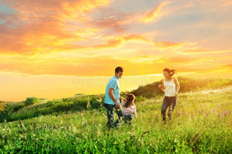 Glückliche Familie, die Spaß draußen hat stockbild
