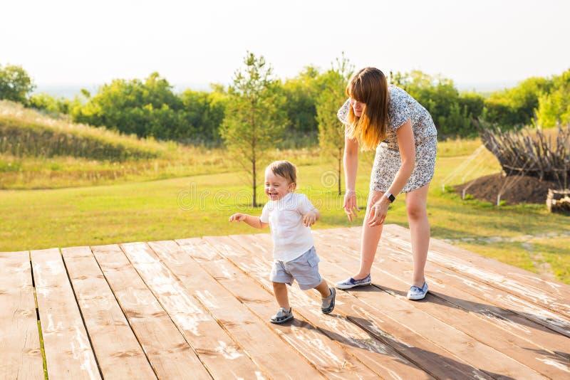 Glückliche Familie, die Spaß hat Baby und seine Mutter, die draußen spielen stockfotos