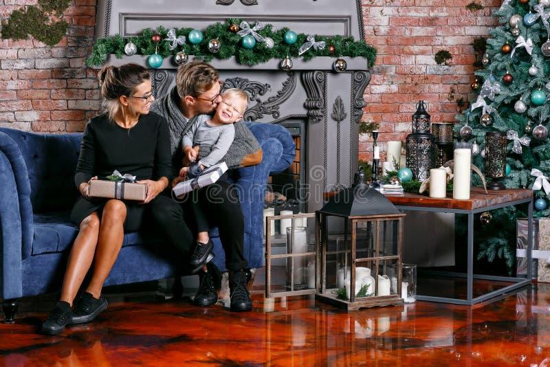Glückliche Familie, die Spaß zu Hause hat Im Dachbodenraum mit Backsteinmauer Junge Eltern mit kleinem Sohn Vater, Mutter und ihr lizenzfreie stockfotos