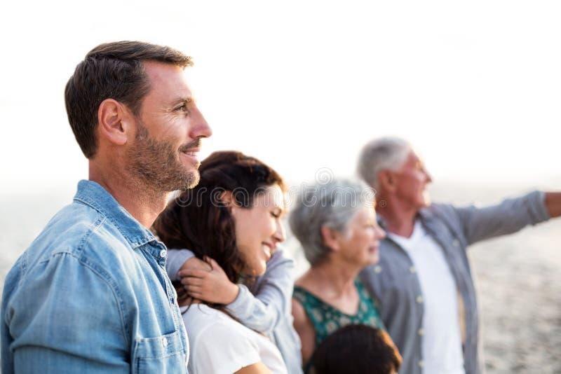 Glückliche Familie, die am Strand aufwirft stockfotos
