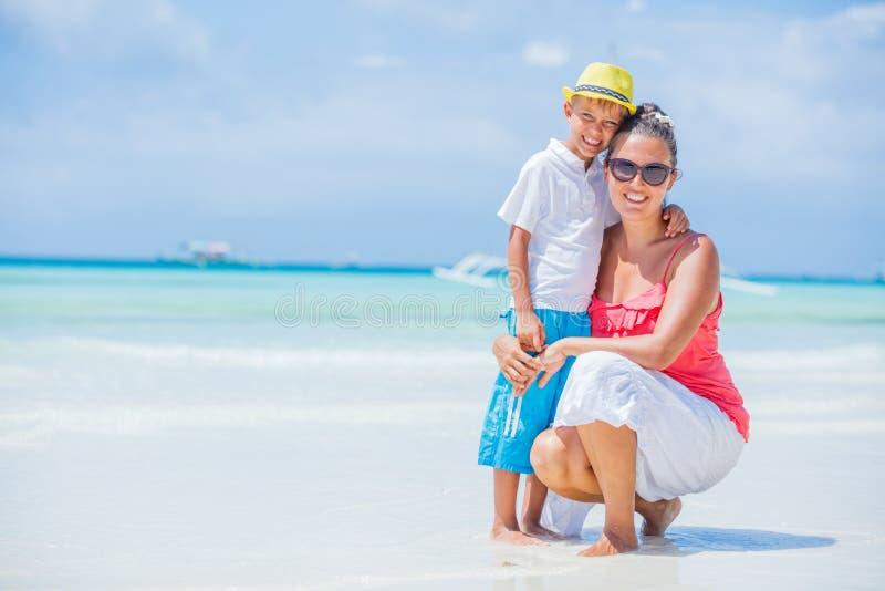Glückliche Familie, die am Strand im Sommer stillsteht Mutter mit dem Jungen, der auf dem Strand stillsteht Junge Mutter und ihr  stockfotos