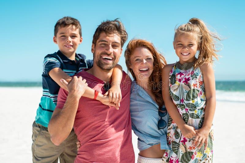 Glückliche Familie, die am Strand lächelt lizenzfreie stockfotografie