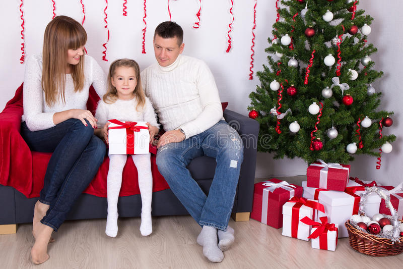 Glückliche Familie, die in verziertem Wohnzimmer mit Weihnachten-tre sitzt lizenzfreie stockfotografie