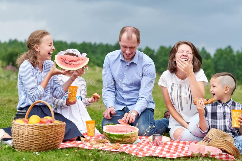 Glückliche Familie, die Wassermelone an einem Picknick isst Picknick in der Wiese oder im Park Junge Freunde und ihre Kinder in d stockfotografie