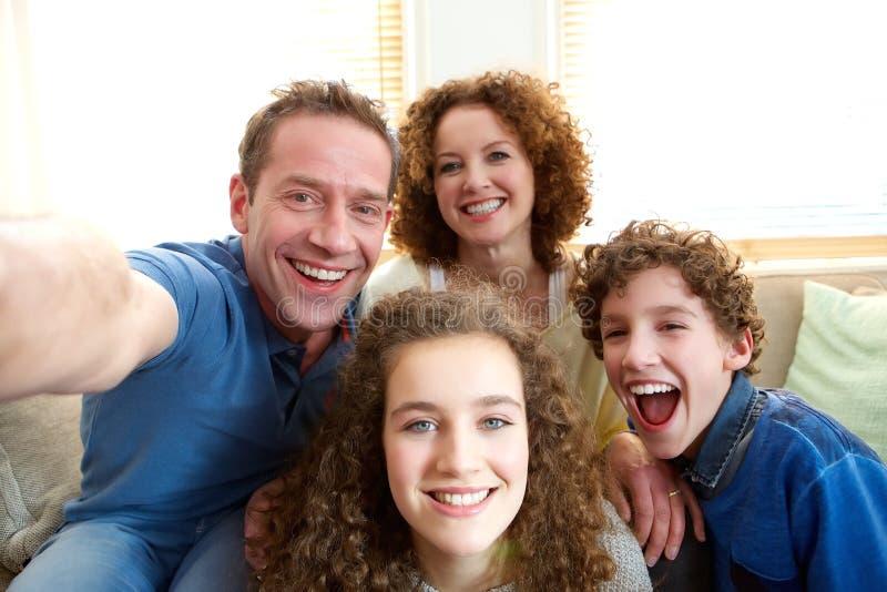 Glückliche Familie, die zu Hause ein selfie nimmt stockfotografie