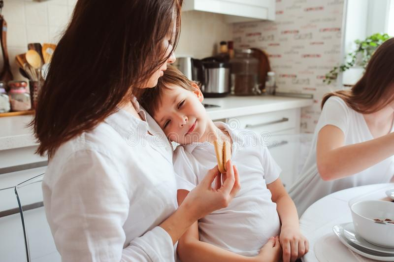 Glückliche Familie, die zu Hause frühstückt Mutter mit zwei Kindern, die morgens in der modernen weißen Küche essen stockfotos
