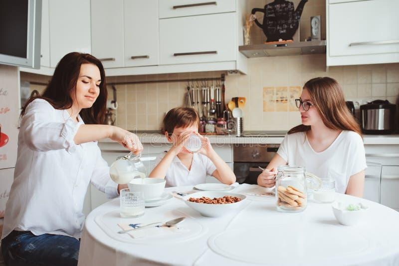 Glückliche Familie, die zu Hause frühstückt Mutter mit zwei Kindern, die morgens in der modernen weißen Küche essen stockfotografie