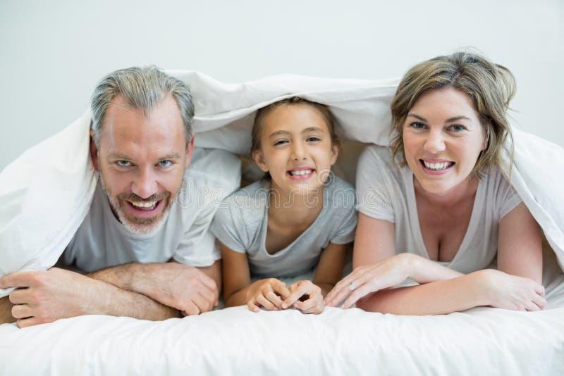Glückliche Familie, die zu Hause unter Decke auf Bett liegt stockfoto