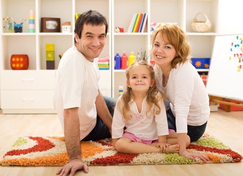 Glückliche Familie, die zusammen auf dem Fußboden sitzt stockbilder
