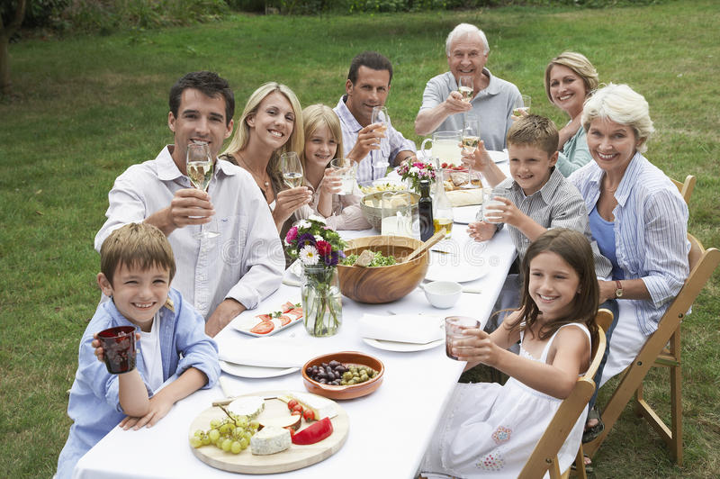 Glückliche Familie, die zusammen im Garten speist lizenzfreies stockfoto