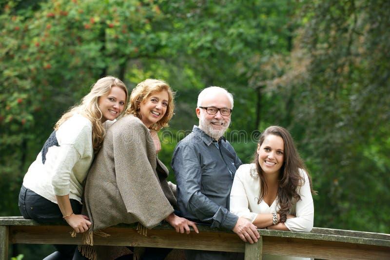 Glückliche Familie, die zusammen im Wald lächelt lizenzfreies stockbild