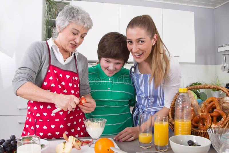 Glückliche Familie, die zusammen mit der Großmutter kocht lizenzfreies stockfoto