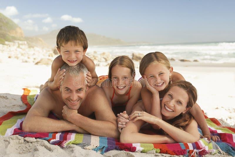 Glückliche Familie, die zusammen am Strand liegt stockbild